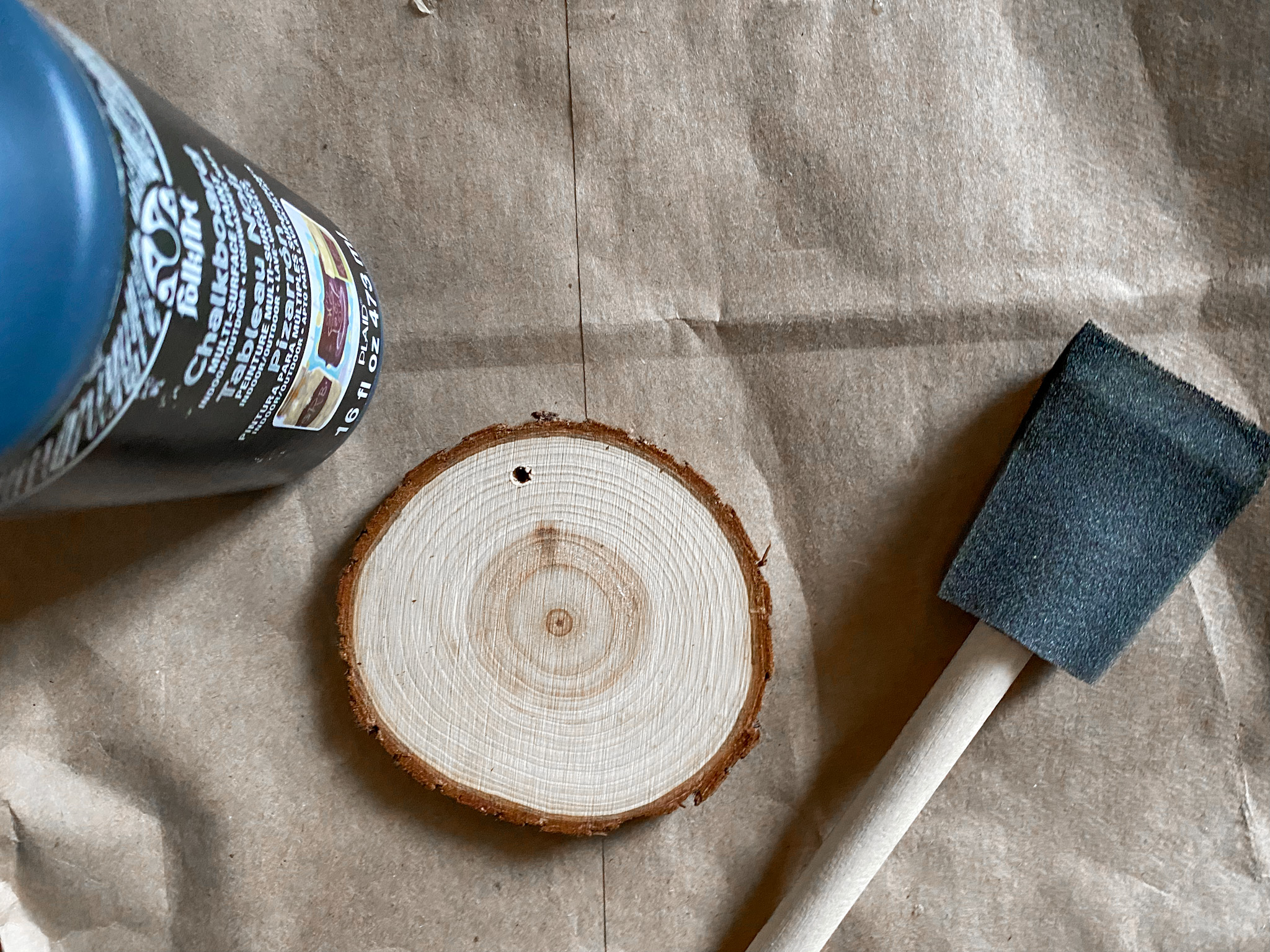Wood slice with chalkboard paint on a brown paper